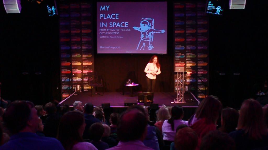 Niamh-presenting-My-Place-in-Space-at-Cheltenham-Science-Festival Niamh Shaw, elon musk, nasa, spacex, engineering, richard branson, communication, stem, astronaut, niamh, scientist, artist, perform, esa, polymath, broadcast, blue origin, virgin galactic, niamh shaw, space exploration, norah patten, zero g, irish astronaut, science communication, women in stem, roscosmos, female astronauts, jaxa, baikonur, irish engineering, ireland's first astronaut, multi disciplined, stem advocate, female space explorer, irelands first female astronaut, irelands first person in space, irish female activist, irish female polymath, irish female role model, irish female trailblazer, irish role models, irish space explorer, performer & communicator & space explorer, space advocate, stem communicator